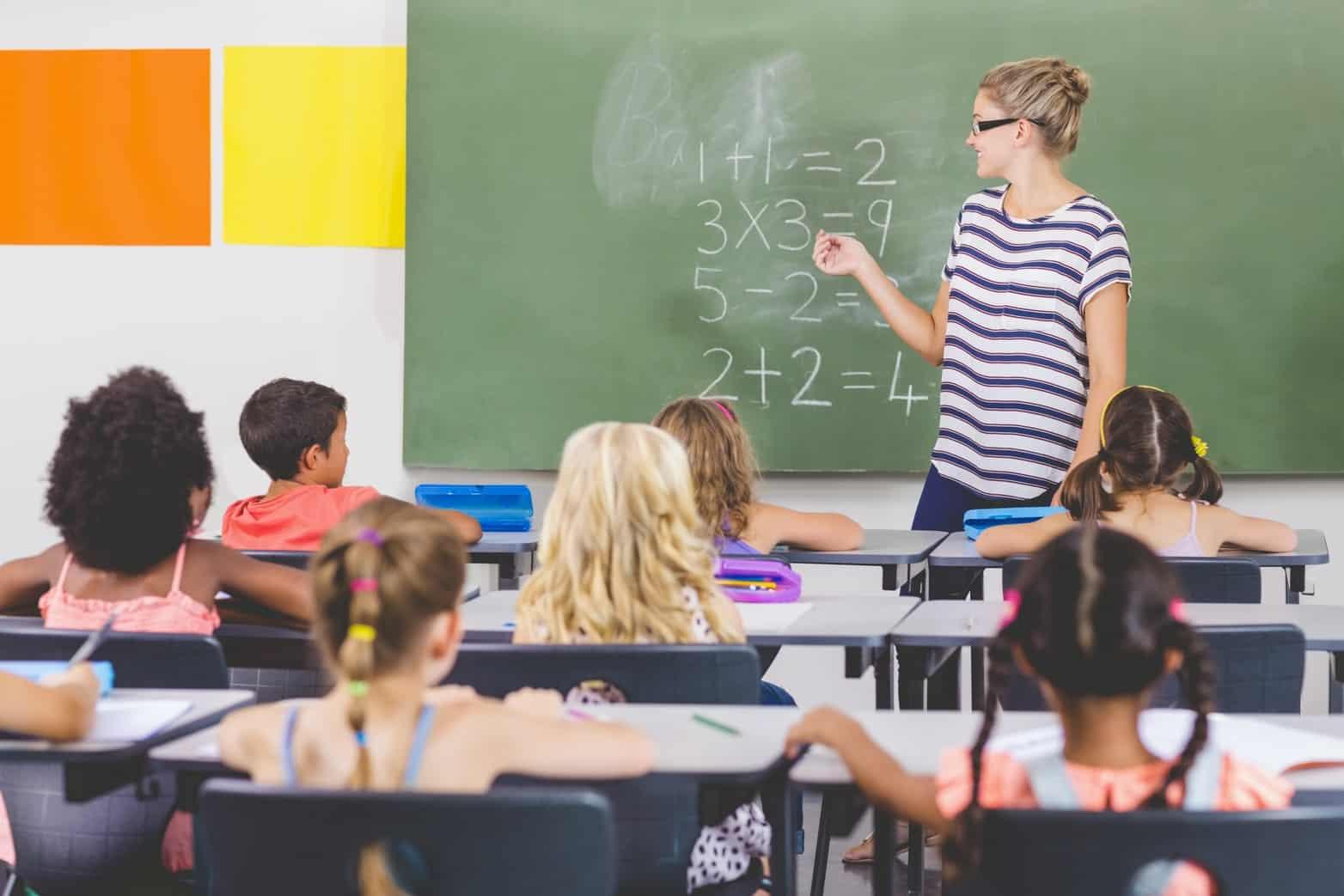 Teacher teaching mathematics to students in a classroom